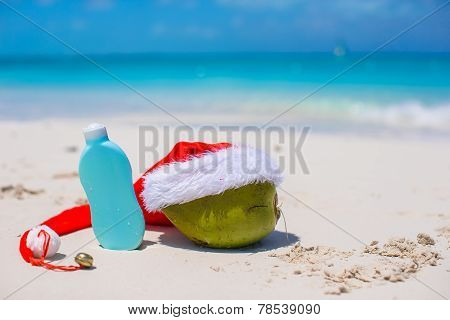 Suncream and Santa Hat on coconut at white exotic beach
