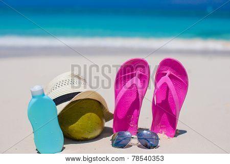 Flip flops, coconut and suncream on white sand