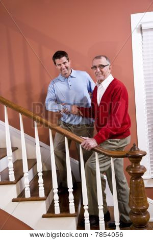 Man Helping Senior Father Climb Stairs At Home