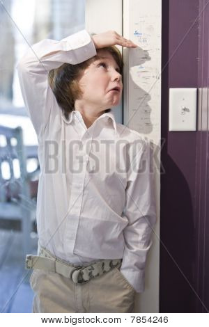 Young Child Measuring Height On Growth Chart