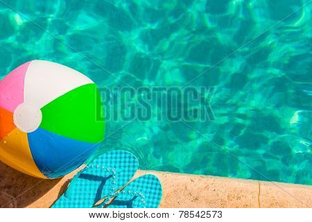 Turquoise Flip Flops And Ball On The Edge Of The Pool