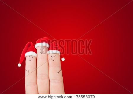 Fingers Faces In Santa Hats Against Red Background. Happy Family Concept For Christmas Or New Year