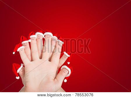 Fingers Faces In Santa Hats Against Red. Holiday Concept For Christmas Or New Years Day.