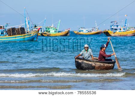 PHAN THIET, VIETNAM - 5 JUNE, 2011: Two fishermen in a coracle boat returning from fishing. Phan Thiet is a coastal city famous for its tourism district Mui Ne and seafood as well as sea products.