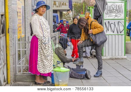 LA PAZ, BOLIVIA, MAY 9, 2014:  Local woman in traditional attire sells fruits compote on street while a bootblack polishes shoes of young woman