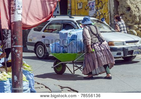 LA PAZ, BOLIVIA, MAY 9, 2014:  Local woman in traditional attire walks down the street pushing a wheelbarrow