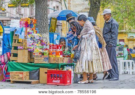 LA PAZ, BOLIVIA, MAY 9, 2014:  Local people buy sweets at street stand at Plaza Murillo