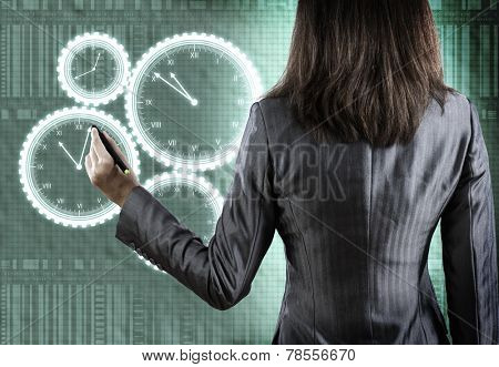 Rear view of businesswoman drawing clock with pen