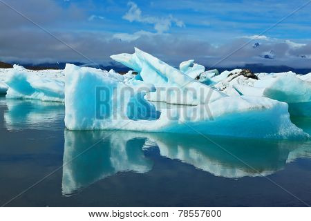 Blue and emerald icebergs and ice floes are reflected in smooth water of the Gulf Yokulsarlon in Iceland. Sunrise.
