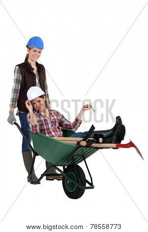 female builder carrying his colleague in a wheelbarrow