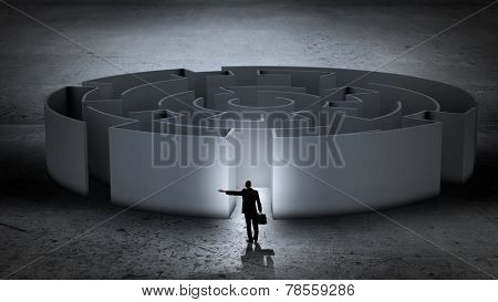 Puzzled businessman standing near entrance of labyrinth