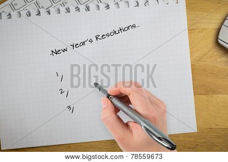 Composite image of new years resolutions against overhead of graph paper on keyboard