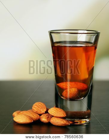 Dessert liqueur Amaretto with almond nuts, on wooden table, on light background