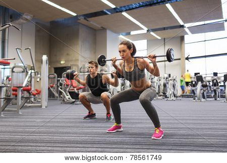 sport, bodybuilding, lifestyle and people concept - young man and woman with barbell flexing muscles and making shoulder press squat in gym