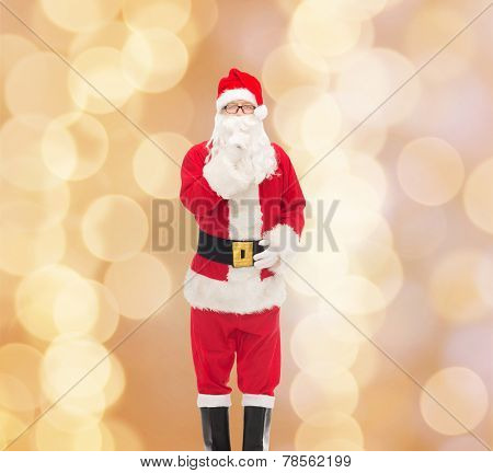christmas, holidays and people concept - man in costume of santa claus making hush gesture over beige lights background