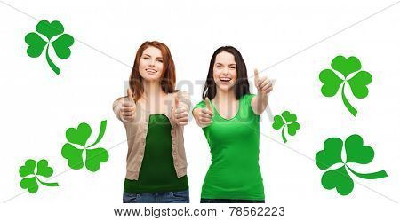 gesture, holidays, st. patricks day and happy people concept - two smiling girls showing thumbs up over white background with green shamrock or clover
