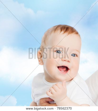 family, child and parenthood concept - close up of mother holding smiling baby