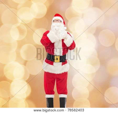 christmas, holidays and people concept - man in costume of santa claus with bag making hush gesture over beige lights background