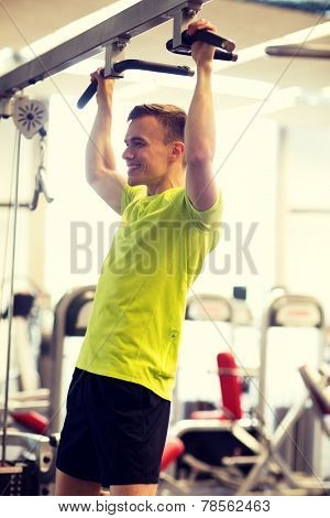 sport, fitness, lifestyle and people concept - smiling man doing pull-ups in gym