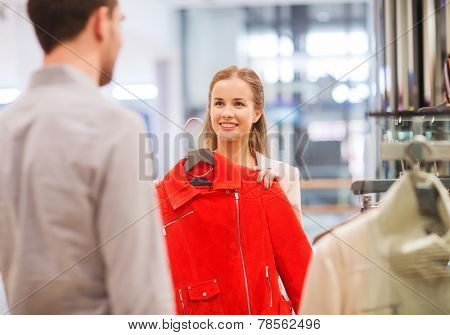 sale, shopping, consumerism and people concept - happy young couple choosing clothes at clothing store in mall
