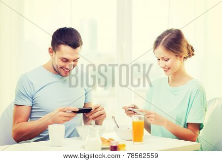 food, home, couple and technology concept - smiling couple with smartphones teaking picture of breakfast at home