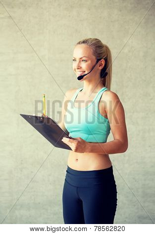 fitness, sport and diet concept - beautiful athletic woman with clipboard in gym