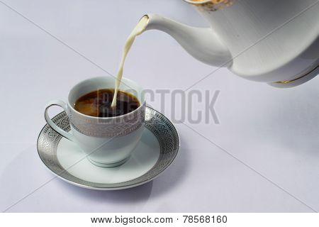 Milk being poured into a cup of coffee