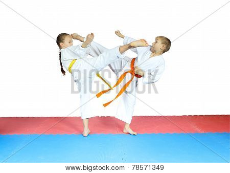 Blows kicks are doing little athletes in karategi