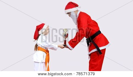 Santa Claus with a black belt is giving little girl in karategi Cup of Karate