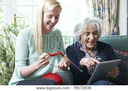 Grandmother Using Digital Tablet Whilst Granddaughter Knits