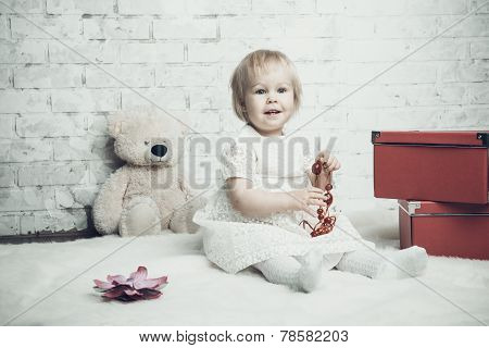 Little Girl With Bright Red Jewellery Posing On Brick Background