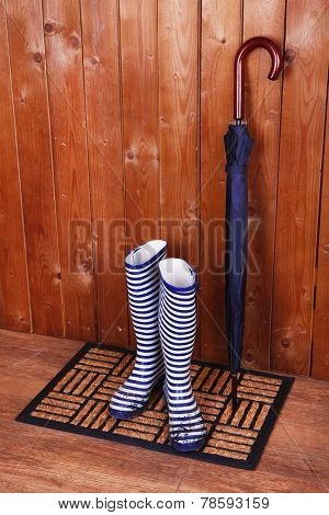 Dirty wellington boots with umbrella on door mat in room
