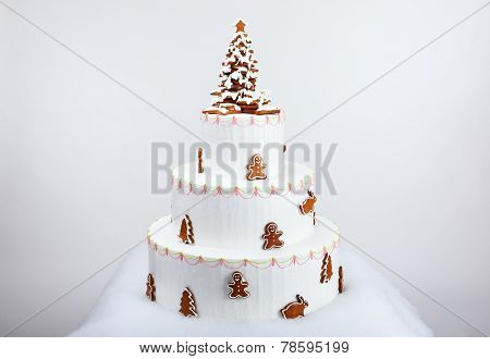 The Artificial Cake Decorated With  Hand-made Eatable Gingerbread Figures And New Year Tree With Sno