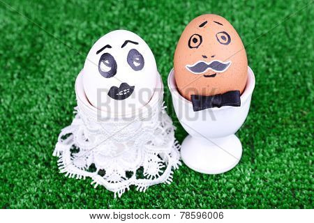 Bride and bridegroom eggs in egg cups on green background