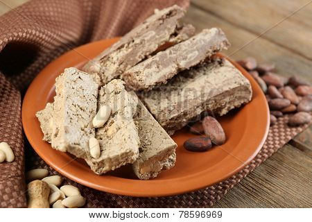 Two kinds of sunflower halva- with cocoa and peanuts on plate, on wooden background