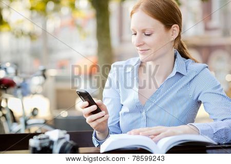 Woman Looks At Mobile Phone In A City