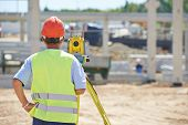pic of theodolite  - Portrait of builder worker with theodolite transit equipment at construction site outdoors during surveyor work - JPG