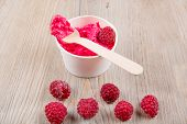 pic of frozen food  - Serving of frozen creamy ice yoghurt with whole fresh raspberries and wooden spoon Healthy bio organic vegan dessert - JPG