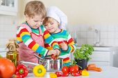 stock photo of vegetable soup  - Two cute little kid boys cooking italian soup and meal with fresh vegetables in home - JPG