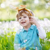picture of bunny ears  - Cute happy little child celebrating Easter holiday and having fun with wearing Easter bunny ears at spring green grass and blooming apple garden outdoors - JPG