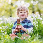 picture of bunny ears  - Happy little toddler boy eating chocolate and wearing Easter bunny ears sitting in blooming garden on warm sunny day - JPG
