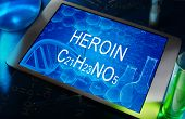 foto of heroin  - the chemical formula of Heroin on a tablet with test tubes - JPG