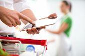 pic of supermarket  - Customer using a digital tablet at supermarket with sales clerk on background - JPG
