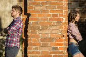 pic of love hurts  - Couple after an argument stands on different sides of the wall - JPG