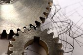 stock photo of mechanical drawing  - Steel cogwheels in connection on drawing in closeup - JPG