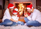 image of chalet interior  - Happy family by fireplace - JPG