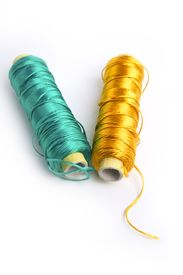 foto of rayon  - metallic rayon thread line spool in green and golden colors over white - JPG