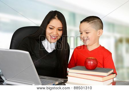Student and teacher looking at laptop and smiling