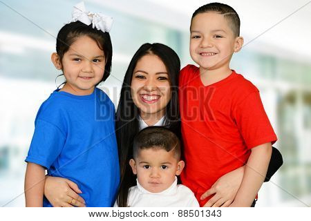Young mother hugging her daughter and two sons