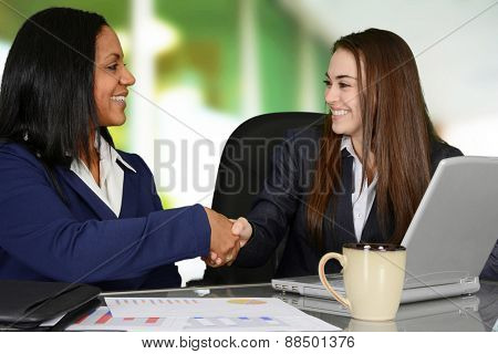 A handshake between two female co-workers in the office